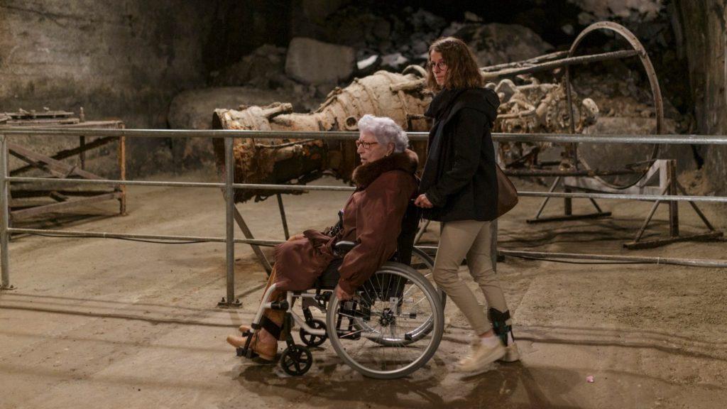 Cena do curta Colette. Nela vemos Collete, uma mulher de 90 anos, branca e com cabelo branco que veste um casaco marrom e está sentada numa cadeira de rodas. Quem está conduzindo a cadeira é Lucie, uma jovem mulher branca que veste um casaco preto e uma calça bege. O fundo da imagem é uma caverna onde eram feitas as produções de foguetes durante a Segunda Guerra Mundial.