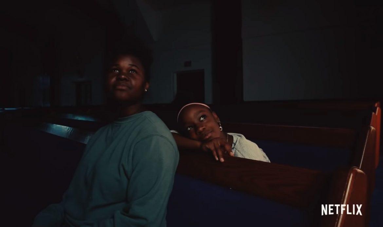 Cena do curta metragem A Love Song For Latasha. Nela vemos duas garotas negras sentadas em bancos de uma igreja. A menina que está sentada no banco da frente, aparenta ser mais velha e veste um moletom verde. Já a outra garota usa um vestido branco e uma tiara rosa no cabelo. As duas estão com expressões sonhadoras e olham para cima. Elas estão em uma igreja com paredes brancas e os bancos são de tecido azul.
