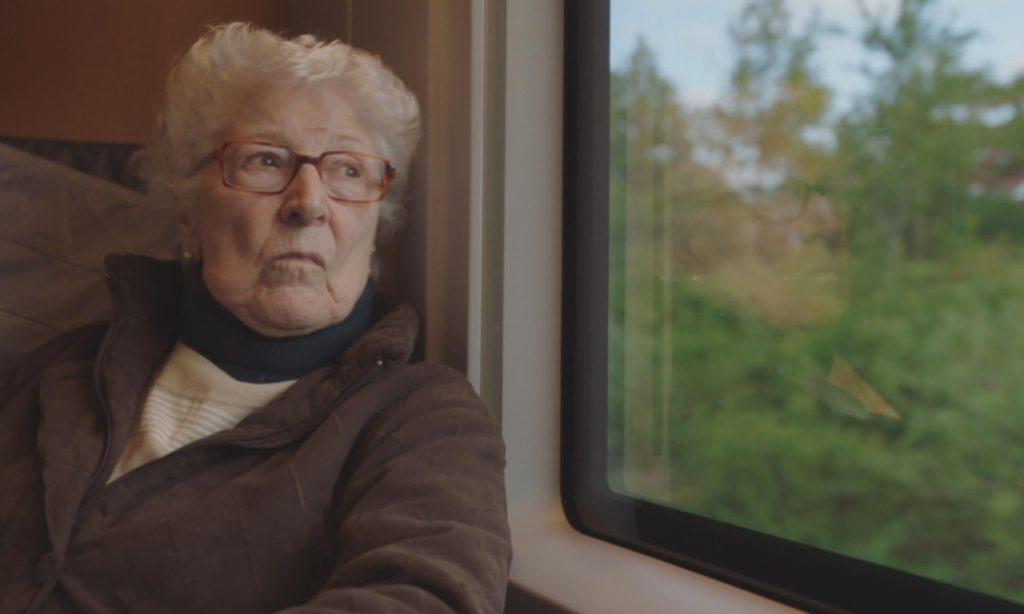 Cena do curta Colette.Nela vemos Collete, uma mulher de 90 anos, branca e com cabelo branco que veste um casaco marrom e está apoiada na janela de um trem. A vista é de várias árvores.