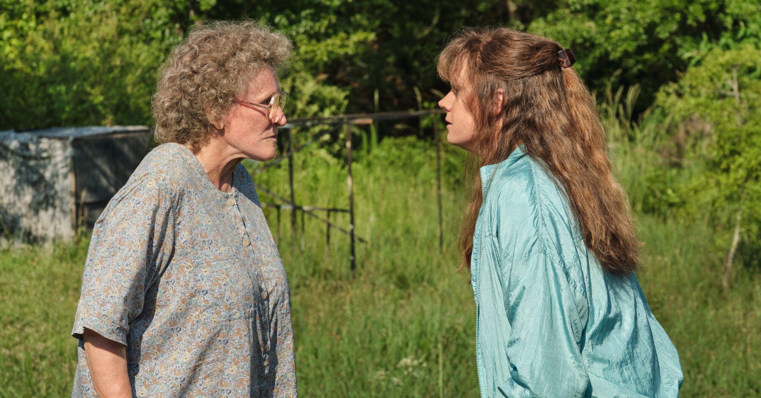 A imagem é uma cena do filme Era uma vez um sonho. Nela, estão as personagens Mamaw e Bev em um gramado, uma encarando a outra. À esquerda, está Mamaw, interpretada por Glenn Close. Ela é uma mulher branca, de cabelos grisalhos e cacheados; ela usa um óculos e está com uma camiseta larga com estampa nas cores azul e bege. À direita, está Bev, interpretada por Amy Adams. Ela é uma mulher branca, de cabelos ruivos compridos; ela veste um agasalho azul-claro.