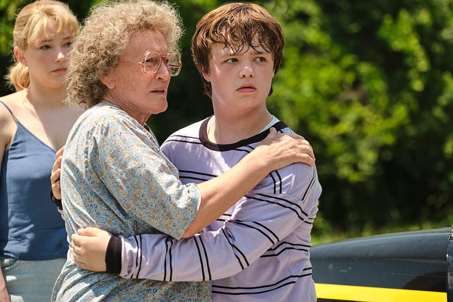 A imagem é uma cena do filme Era uma vez um sonho. Nela, estão os personagens Lindsay, Mamaw e J. D. À esquerda, está Mamaw, interpretada pela atriz Glenn Close. Ela é uma mulher branca, de cabelos grisalhos e cacheados; ela usa um óculos e está com uma camiseta larga com estampa nas cores azul e bege, e com os braços nos ombros de J. D. Vance. À direita, com os braços em volta de Mamaw, está J. D., em sua fase adolescente, interpretado pelo ator-mirim Owen Asztalos. Owen é um menino branco, de cabelos castanhos claros; ele veste uma blusa branca de mangas-compridas com listras pretas. No canto esquerdo, atrás de Mamaw, está Lindsay, interpretada pela atriz Haley Bennett. Ela é uma mulher branca, com cabelos loiros amarrados em um coque baixo; ela veste uma regata azul e uma calça jeans.