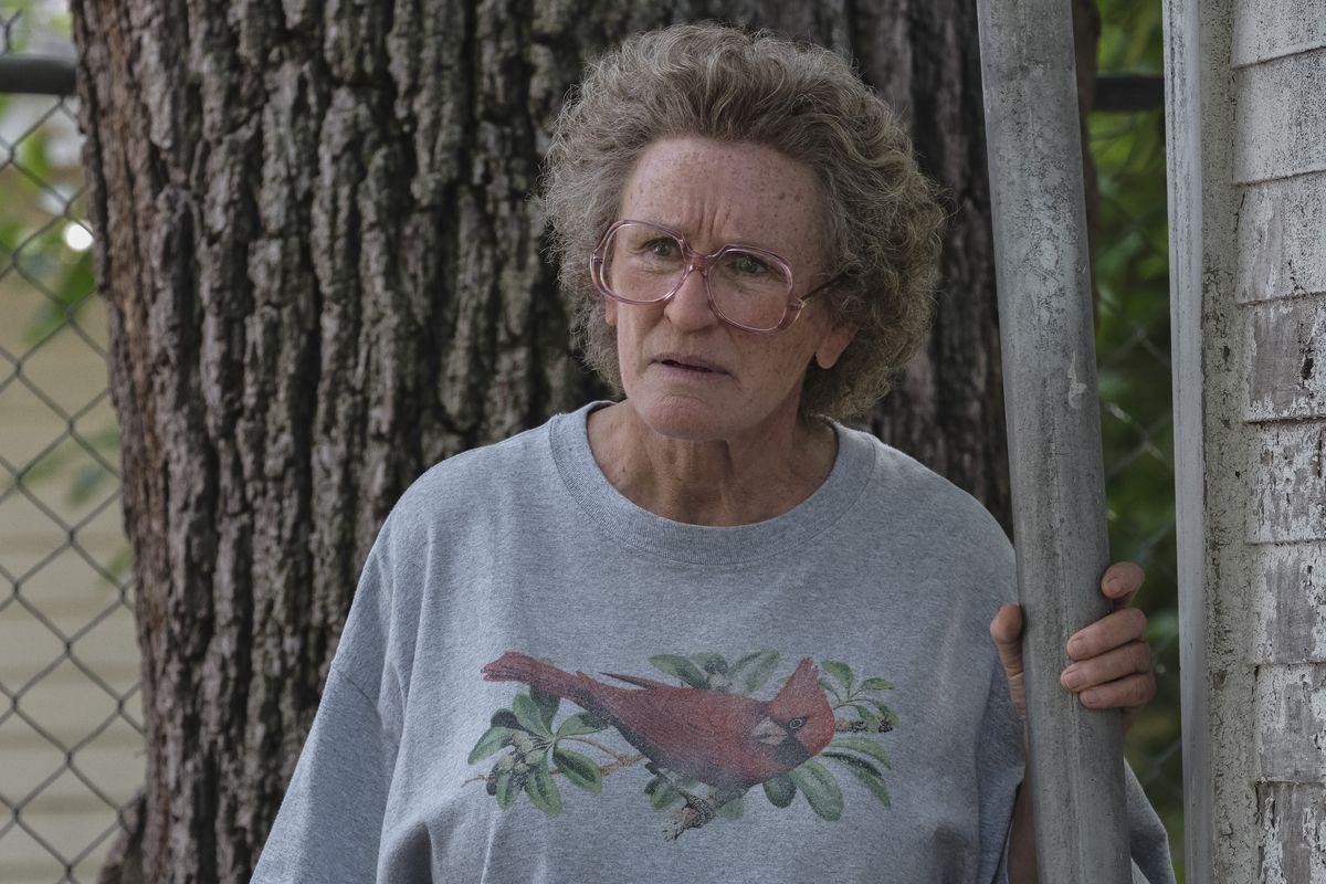 A imagem é uma cena do filme Era uma vez um sonho. Nela, está a personagem Mamaw, interpretada pela atriz Glenn Close, no canto de uma casa, com a mão esquerda segurando em um cano. Ela é uma mulher branca, de cabelos grisalhos e cacheados; ela usa um óculos e está com uma camiseta larga cinza com o desenho de um pássaro.