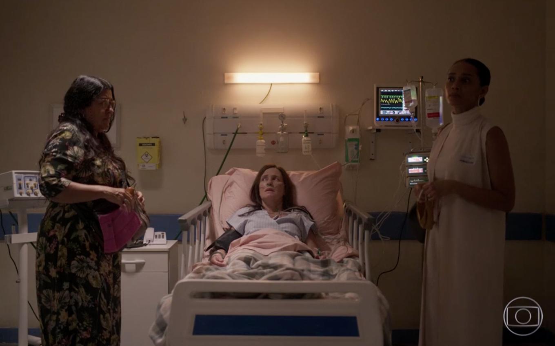 Cena da novela Amor de Mãe. Na imagem, as personagens Lurdes, Thelma e Vitória estão em uma sala do hospital. Lurdes, interpretada por Regina Casé, está ao lado esquerdo; ela é uma mulher branca, de cabelos compridos escuros, e veste um vestido florido e usa uma bolsa. Ao centro, está Thelma, interpretada por Adriana Esteves, internada em uma cama de hospital. Ela é uma mulher branca, de cabelos castanhos e está com avental de hospital. Ao lado direito, está Vitória, interpretada por Tais Araújo. Ela é uma mulher negra, com cabelos presos em um coque baixo; ela veste uma blusa branca de gola alta, um colete e calça brancos.