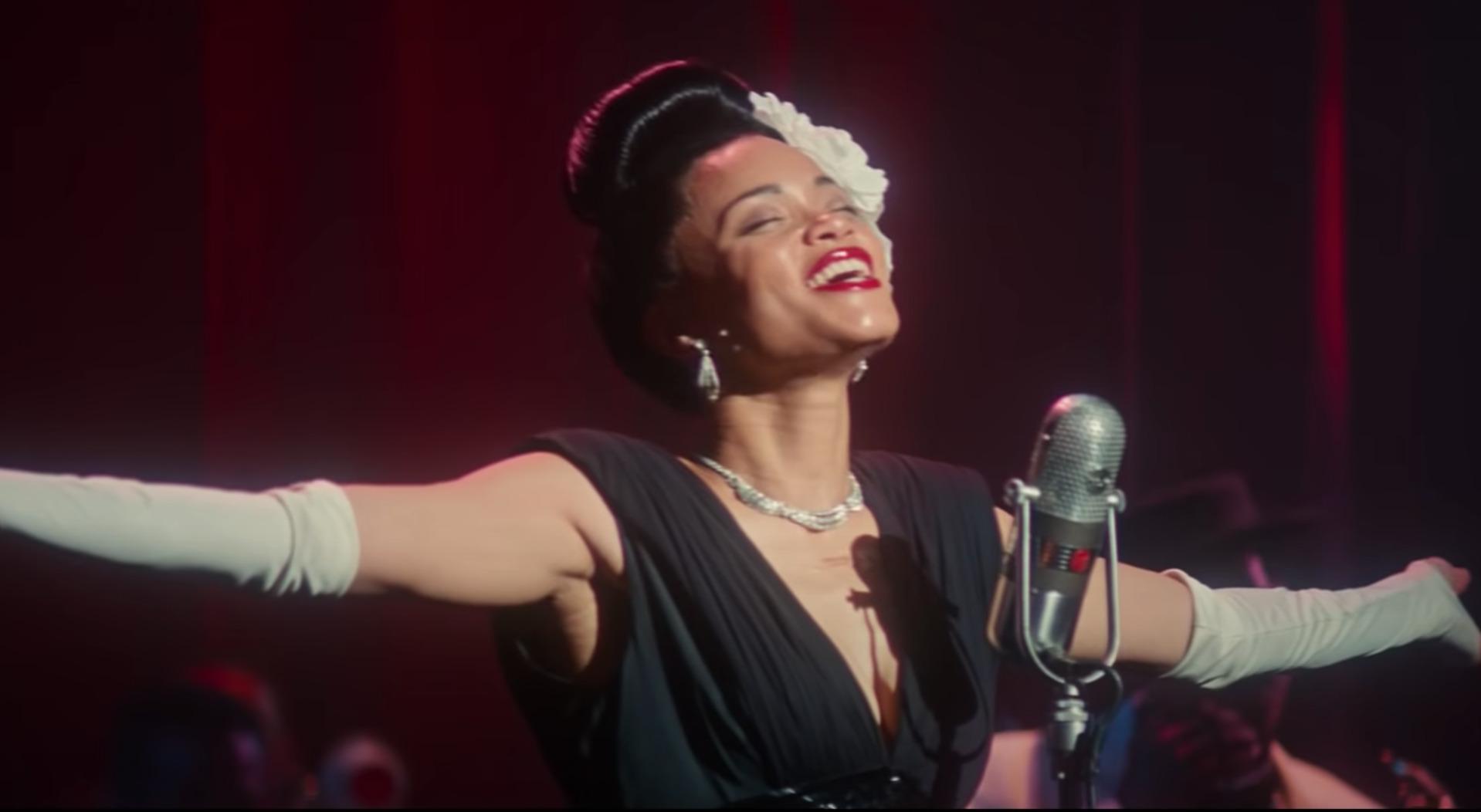 Cena do filme Estados Unidos Vs Billie Holiday. Na imagem, vemos Billie Holiday, interpretada por Andra Day, em frente a um microfone, com os braços abertos. Ela é uma mulher negra, de cabelos escuros presos em um coque no topo da cabeça, com uma flor branca ao lado esquerdo. Billie veste um vestido preto, luvas brancas compridas, um par de brincos e um colar. Ela está sorrindo e com os olhos fechados.