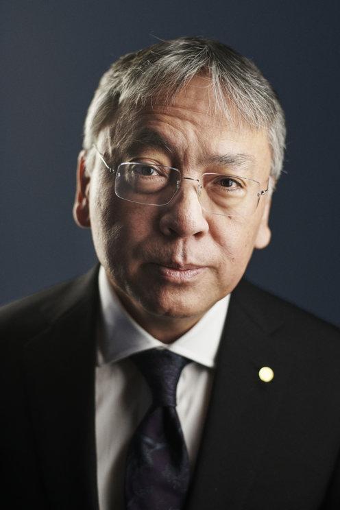 Foto do escritor Kazuo Ishiguro. Ele é um homem ásiatico com cabelos brancos e olhos castanhos, ele usa um óculos fino, veste um terno preto com uma gravata azul. O fundo atrás do autor é azul escuro.