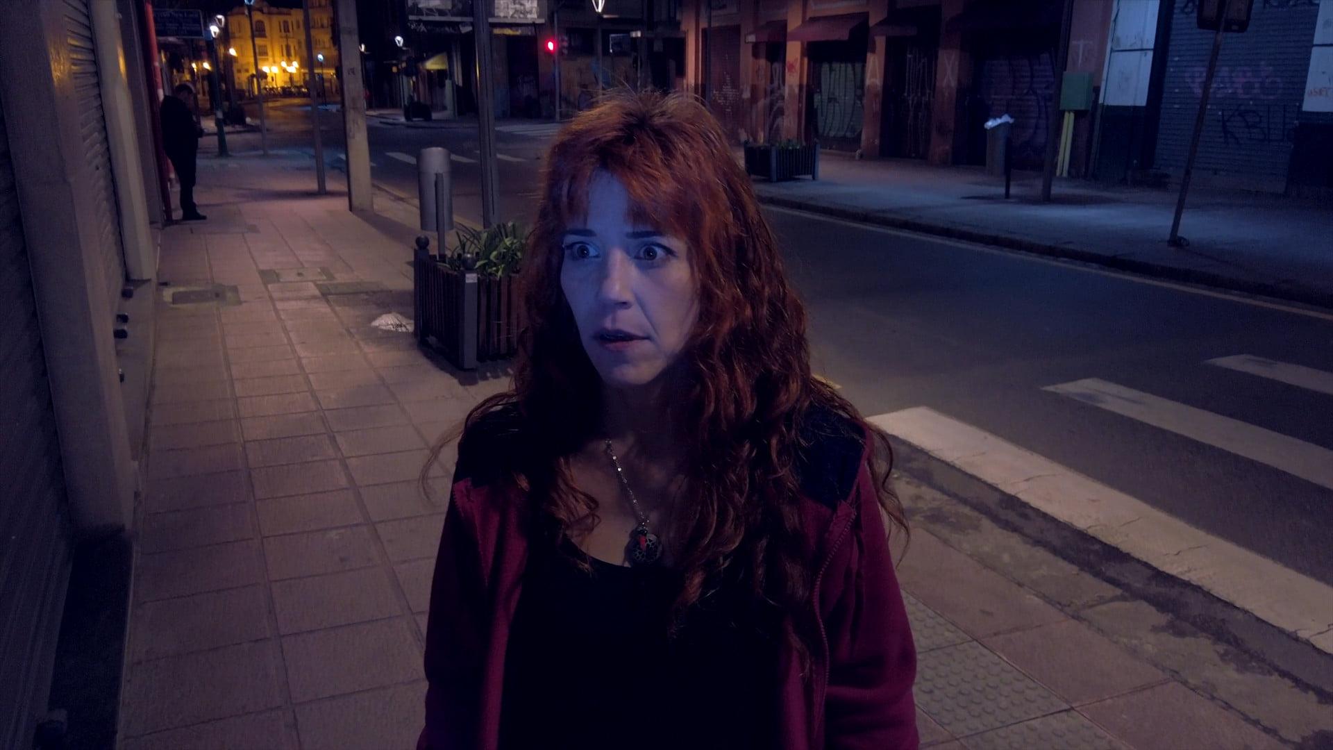 Cena do curta It's a Match. Nela, vemos uma mulher ruiva na rua e, ao fundo, seu perseguidor, todo de preto. Está de noite.