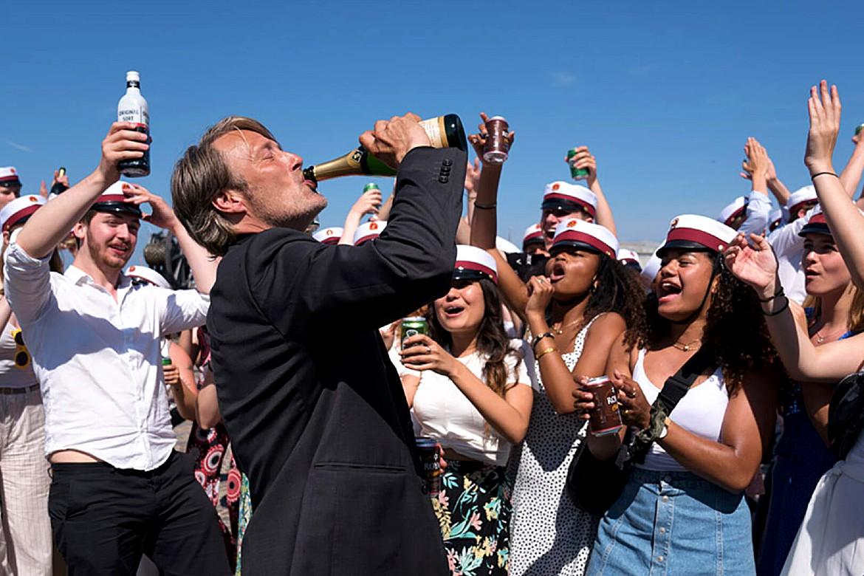 Cena do filme Druk - Mais uma Rodada. Centralizado e ligeiramente à esquerda vemos Mads Mikkelsen tomando champagne diretamente da garrafa. Ele usa um paletó preto enquanto a luz do sol bate em seu corpo. Ao fundo, vários jovens homens e mulheres celebram, animam e aplaudem a atitude de Mads. Todos eles usam um chapéu de navegador e também carregam cervejas em suas mãos. Atrás de todos podemos ver o céu totalmente azul e sem nuvens.