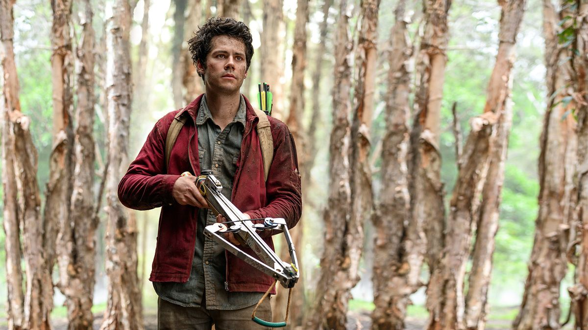Cena do filme Love & Monsters. Dylan O'brien, homem branco de cabelo escuro curto, está de pé segurando uma arma. Ele veste calça e blusa verde escura, e uma jaqueta vermelha por cima. No fundo há troncos de árvores. Ele olha para o lado direito da imagem, o rosto machucado com uma expressão assustada.