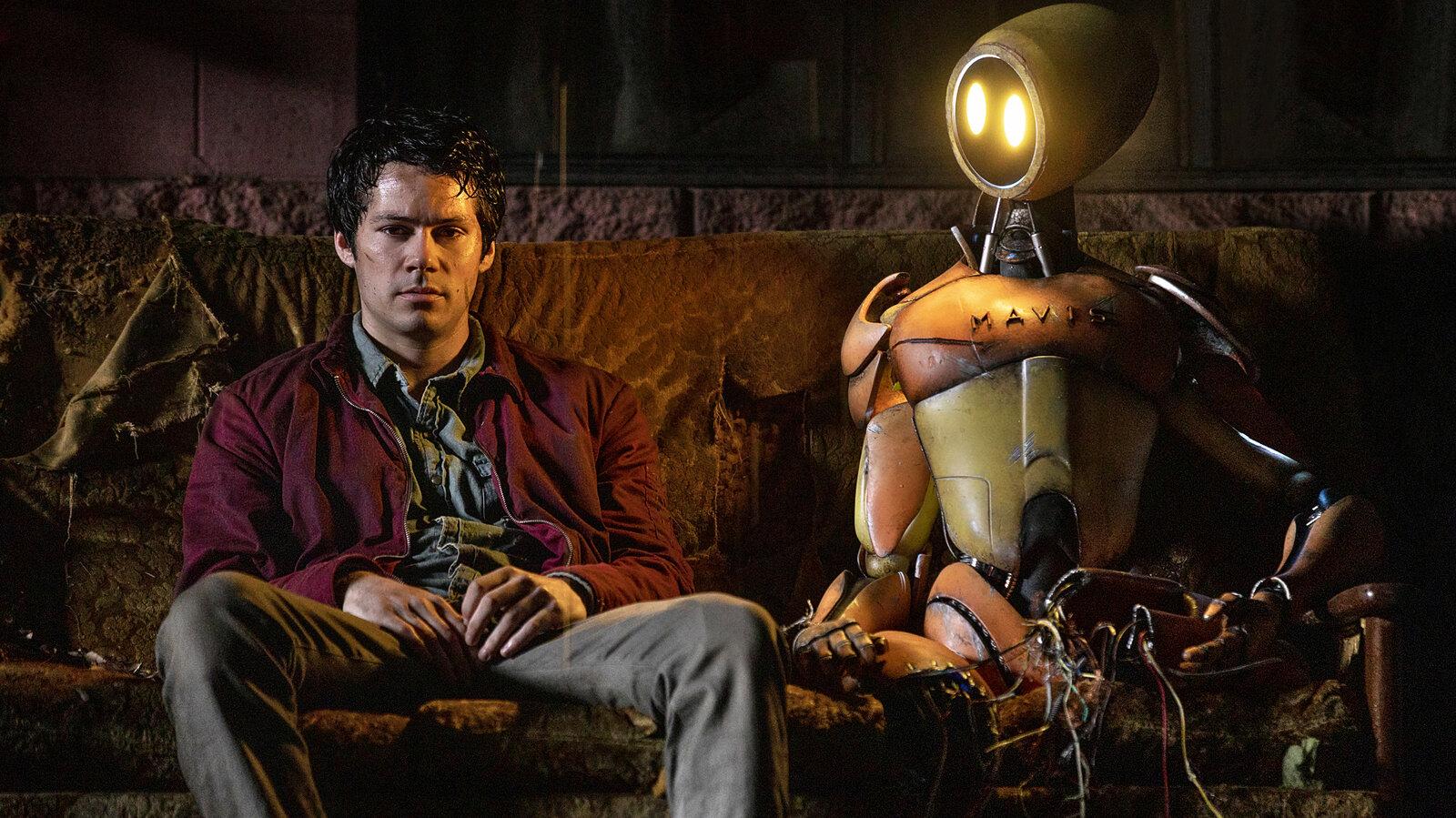 Cena do filme Love & Monsters. Em um sofá laranja, Dylan O'brien está sentado. Homem branco de cabelo escuro curto, ele veste blusa azul, jaqueta vermelha e calça jeans. O jovem olha para baixo, e tem o seu rosto iluminado pela luz que sai do robô ao seu lado. O robô é laranja e amarelo, do mesmo tamanho de Dylan.