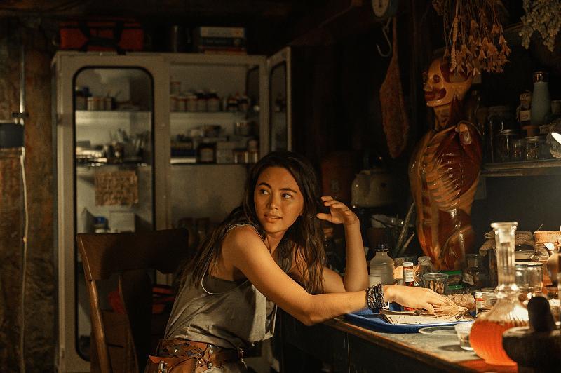 Cena do filme Love & Monsters. A atriz Jessica Henwick, mulher asiática, está sentada, olhando para o lado direito da imagem. Ela tem seu cabelo escuro solto e veste uma regata cinza. Em uma cadeira de madeira, ela encosta o braço na mesa a sua frente que está repleta de objetos. No fundo da imagem há um armário cinza. A foto é iluminada por uma luz de tom amarelado.