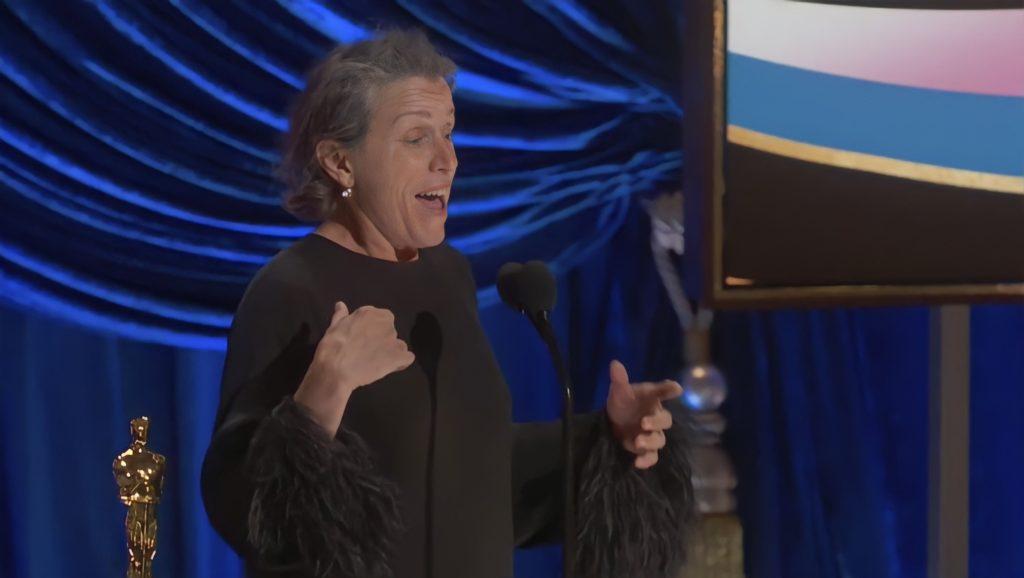 Foto de Frances McDormand. A mulher branca, de cabelos grisalhos, olha com entusiasmo para frente, enquanto fala no microfone. Ela veste roupas pretas. Do seu lado esquerdo há a estatueta do Oscar, e o fundo é azul, com uma tela com desenhos coloridos.