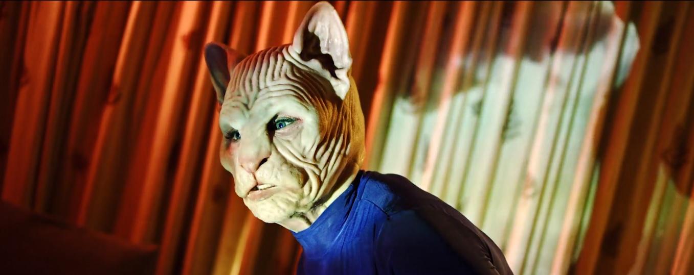 Cena do curta #MeowToo. Nela, vemos uma cena grotesca, de uma mulher usando uma máscara realista de gato, suas feições são medonhas, e a iluminação em foco deixa tudo mais estranho. Ao fundo, está uma cortina alaranjada.