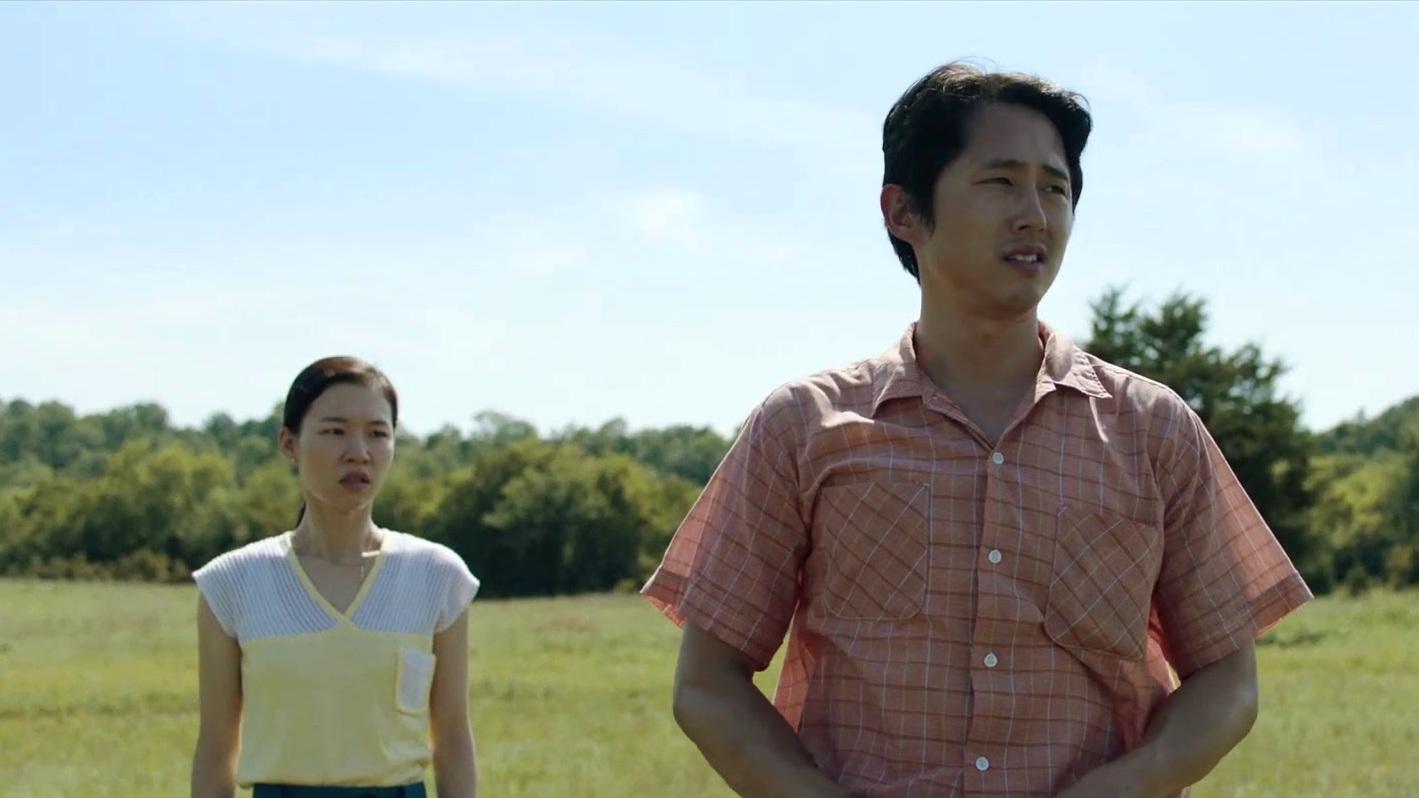 Cena do filme Minari. A imagem mostra a personagem Monica, interpretada por Ye-ri Han, uma mulher asiática de cabelos castanhos lisos presos num rabo baixo, no lado esquerdo. Ela veste uma camiseta amarela clara e aparece da cintura para cima, olhando para Jacob, que está a sua frente, mais à direita da imagem. O personagem é interpretado por Steven Yeun, um homem amarelo, de cabelos lisos escuros, e veste uma camisa de mangas curtas xadrez alaranjada. Ele olha para fora da imagem, no lado esquerdo. Os casal está num campo, o céu é azul e ao funde pode-se observar muitas árvores.