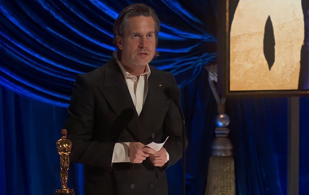 Foto de Mikkel E. G. Nielsen. O homem branco, com cabelos grisalhos e de jaqueta preta por cima de uma blusa branca, segura um papel enquanto fala no microfone. Do seu lado esquerdo está a sua estatueta, o fundo é azul e possui uma tela bege.