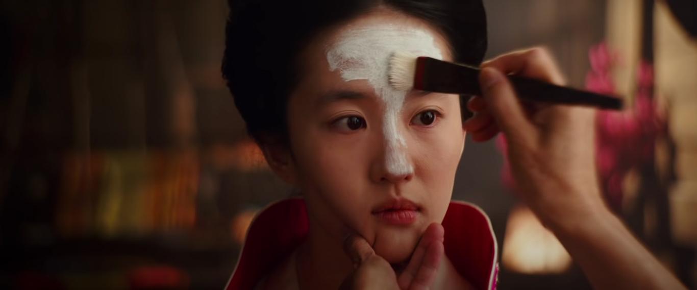 Fotografia retangular de uma cena de Mulan. A atriz Liu Yifei está no centro da imagem, do pescoço até o final da testa. Liu é chinesa, com cabelos pretos presos acima da cabeça e olhos castanhos escuros, quase pretos. Ela veste um kimono chinês antigo vermelho. A mão esquerda de outra pessoa segura seu queixo enquanto a direita segura um pincel e passa tinta branca por sua testa. O nariz da atriz também está semi pintado de branco. O fundo está desfocado, mas no lado direito da imagem pode-se observar flores rosas.