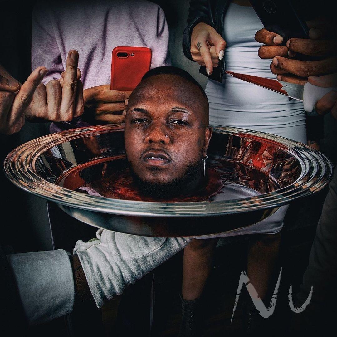 Capa do disco NU, de Djonga. A imagem mostra a cabeça de Djonga decepada em uma bandeja de prata, como se estivesse sendo servida. Em volta, pessoas estão apontando celulares para ele como se tirassem fotos, e também apontando o dedo do meio.