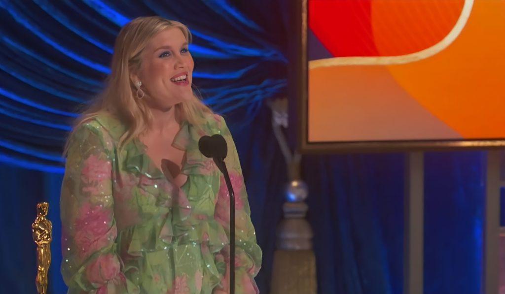 Foto de Emerald Fennell. Uma mulher branca, gorda e loira, ela veste um vestido verde com detalhes em rosa. A mulher está de pé atrás de um microfone, olhando para frente com um sorriso. O fundo é azul com uma tela laranja, e do seu lado esquerdo há uma estatueta.