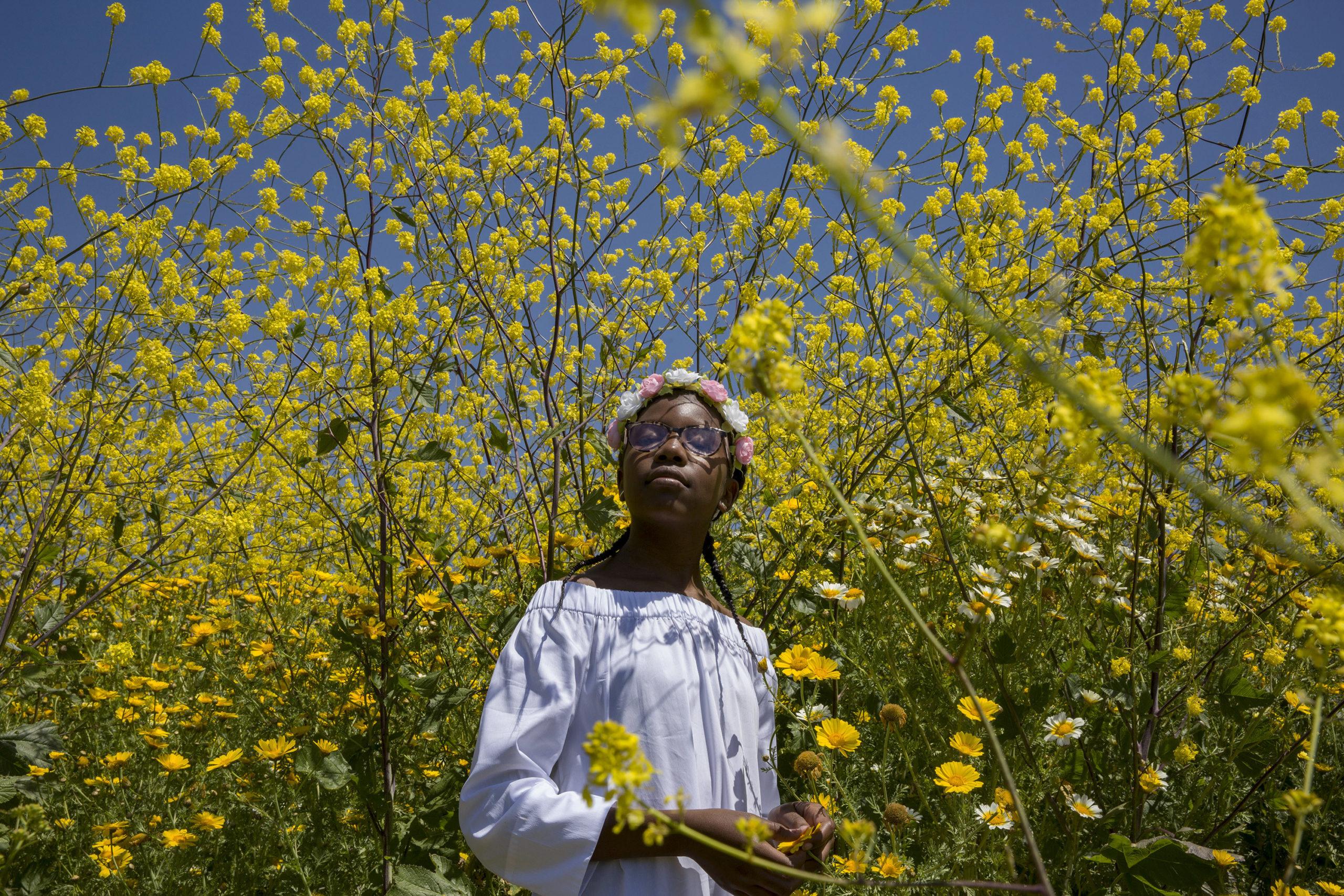 Cena do curta metragem A Love Song For Latasha. Nela vemos uma garota negra em um jardim. A menina veste um vestido de mangas longas na cor branca, está com duas tranças e uma tira de flores rosa e branca no cabelo. Ela usa um óculos de armadura redonda. O jardim é repleto de flores amarelas e brancas.