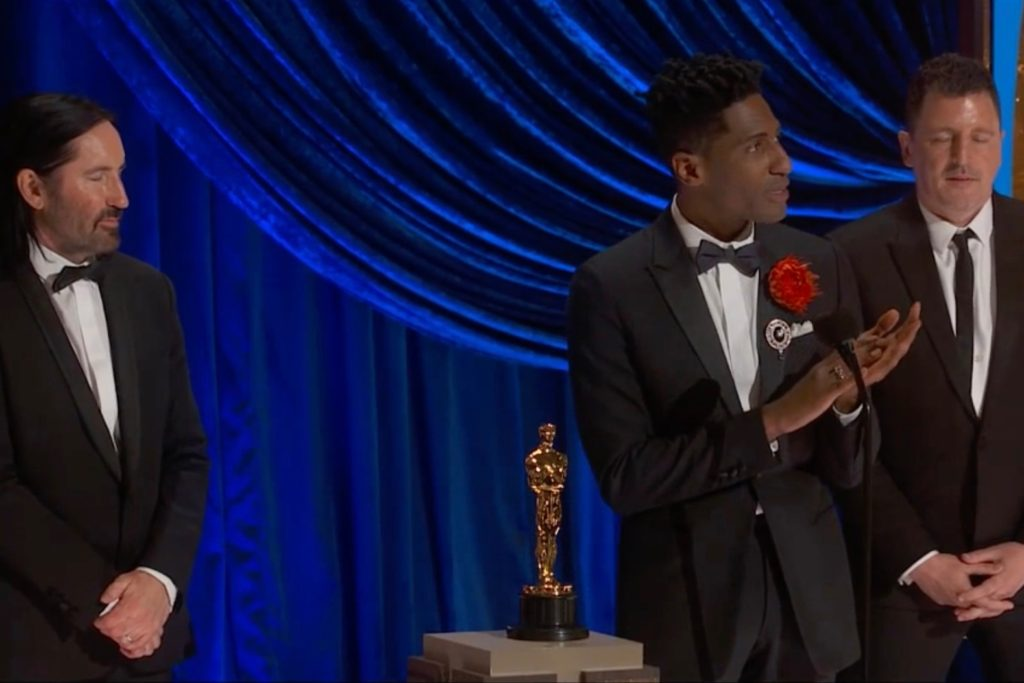 Foto de Jon Batiste, Trent Reznor e Atticus Ross. Jon, homem negro de cabelos curtos, está no meio, vestindo um terno preto com uma rosa vermelha pendurada. Ao seu lado esquerdo e direito estão os homens brancos, também de terno preto, o olhando enquanto ele discursa. No centro da imagem há a estatueta do Oscar, e o fundo é azul.