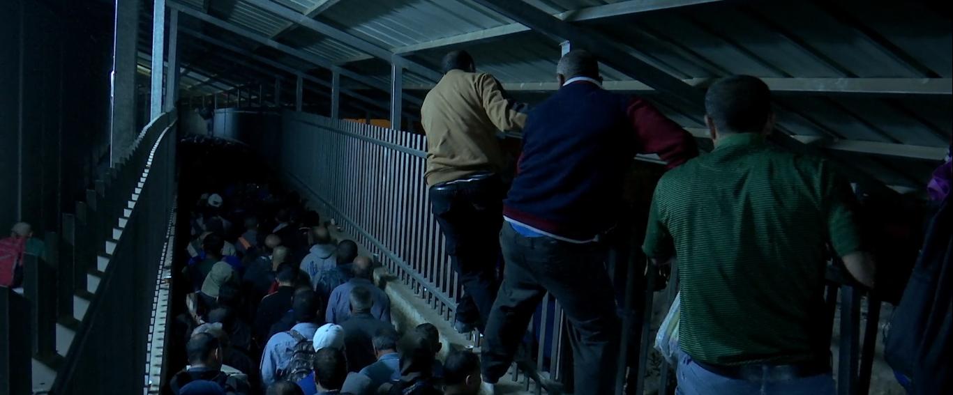 Cena do filme The Present. A cena foi gravada no Checkpoint 300, um posto de checagem entre a Cisjordânia e Israel. Na imagem há um grande corredor em direção ao fundo da fotografia, cercado por paredes e grades. Muitas pessoas estão passando por esse corredor, de forma amontoada. Algumas pessoas atravessam escalando as grades no alto.