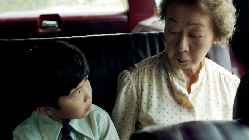 Cena do filme Minari. A imagem mostra David, personagem de Alan Kim, uma criança amarela, e Soonja, personagem de Yuh-Jung Youn, uma senhora asiática. Eles estão no banco de trás de um carro, e se olham desconfiados. David veste uma camisa verde clara e uma gravatinha azul escura, e Soonja veste uma camisa amarela clara de bolinhas.