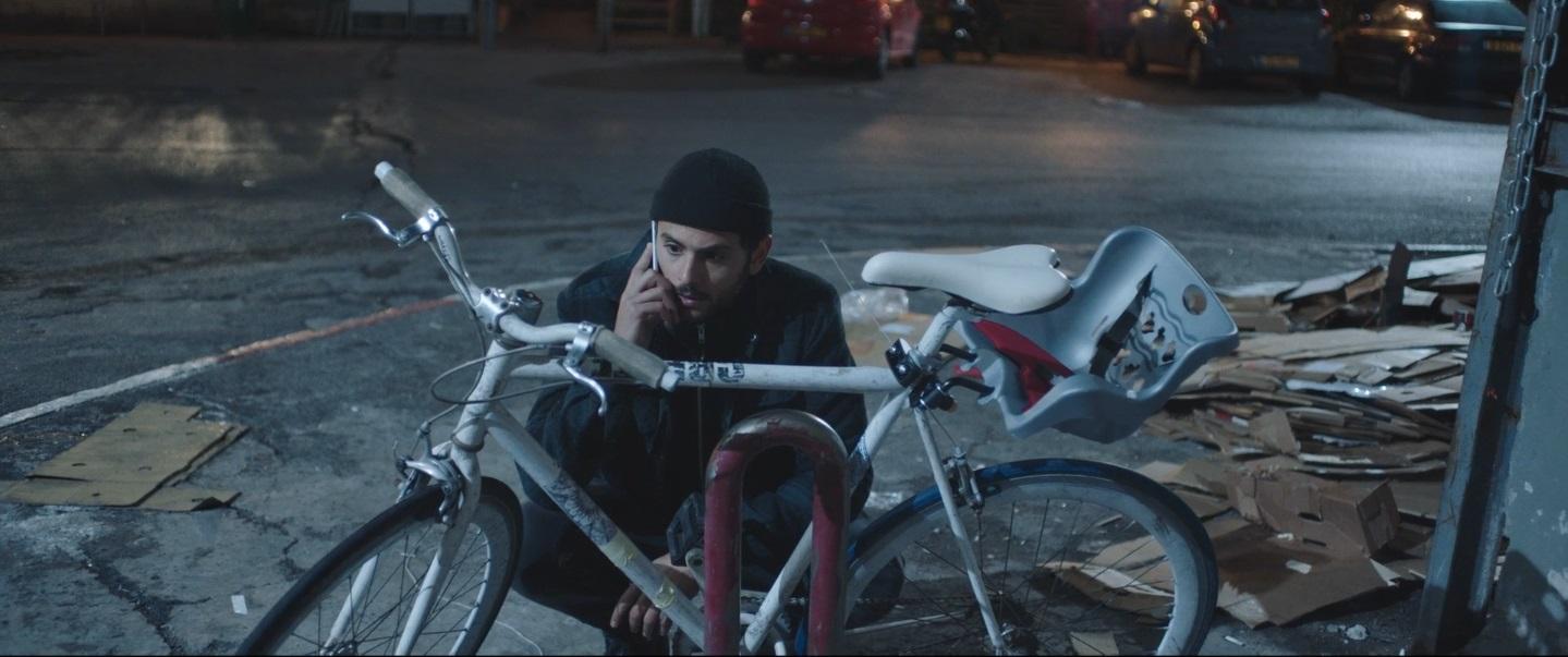 Cena do curta White Eye. A imagem é retangular e centralizada nela está Daniel Gad e uma bicicleta. Daniel é um homem branco com barba e bigode escuro. Ele usa uma touca, uma jaqueta e calça pretas, está agachado e segura o celular no ouvido com a mão direita. A sua frente, está uma bicicleta com uma cadeirinha infantil atrás do banco. Os dois estão numa esquina de uma rua escura.