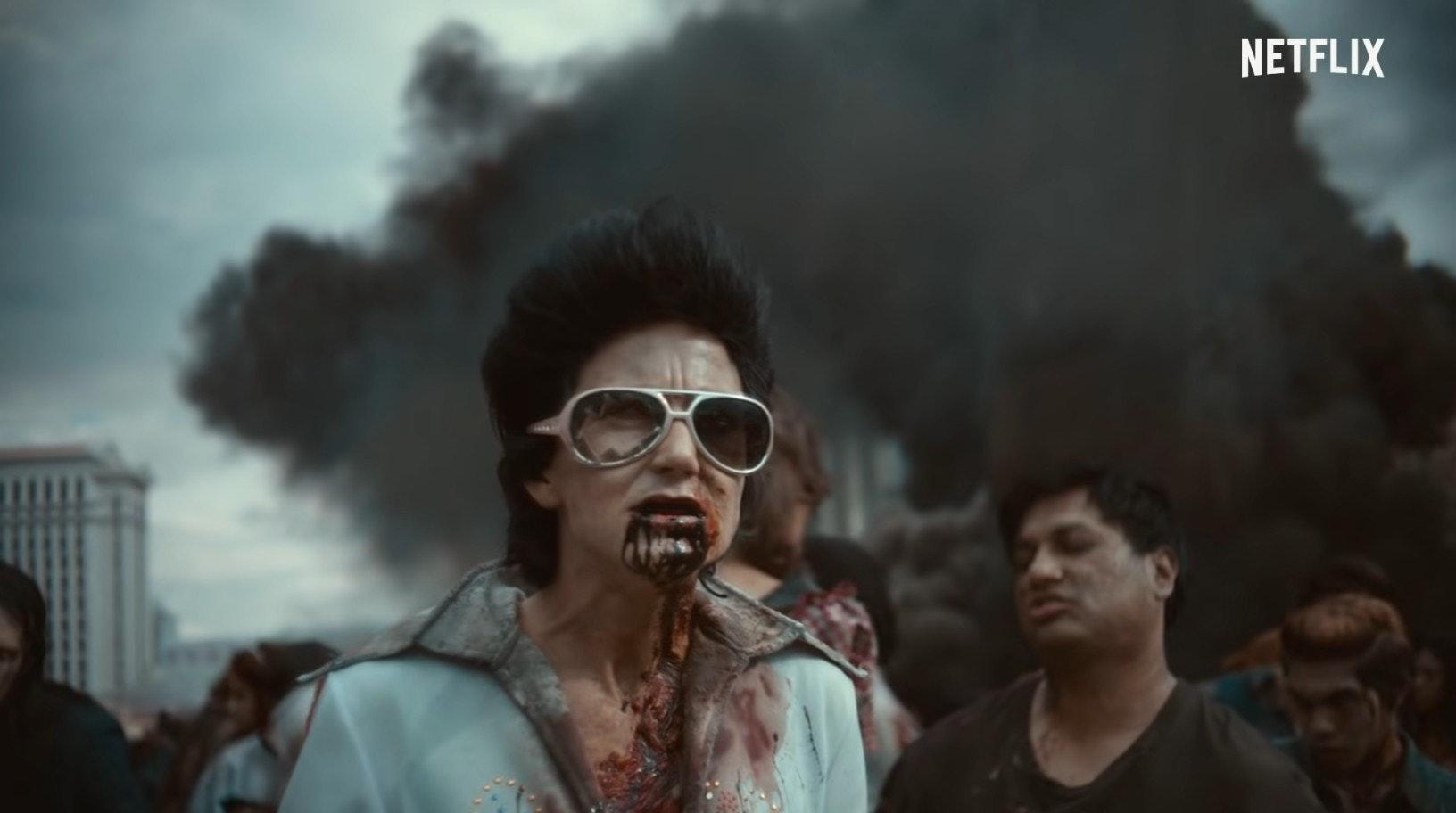 Cena de Army of the Dead. No centro, vemos um zumbi - um homem branco vestido de Elvis com múltiplas escoriações e sangue escorrendo por sua boca. Ele usa um macacão branco, também sujo de sangue. Ao fundo, vemos outras criaturas e a fumaça preta de uma explosão.