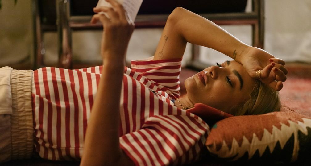 Cena do filme Me sinto bem com você. Nela, vemos Manu Gavassi deitada com um papel em mãos. Ela é magra, branca e tem os cabelos loiros na altura do ombro. Ela veste uma camiseta listrada vermelha e branca.