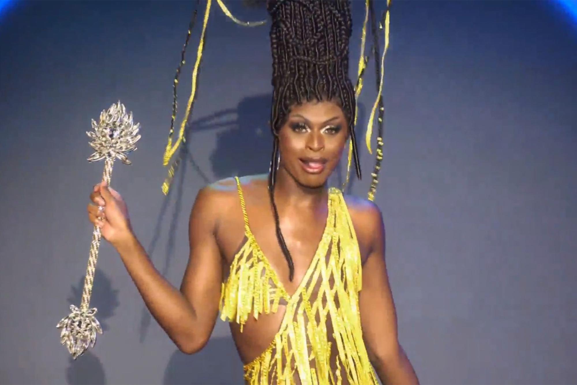 Cena da 13ª temporada do reality show RuPaul's Drag Race. Nela, vemos Symone, drag negra, magra e de peruca preta com adornos de confete dourados, andando com um cetro prateado. Seu vestido segue o mesmo padrão amarelo dos confetes do cabelo
