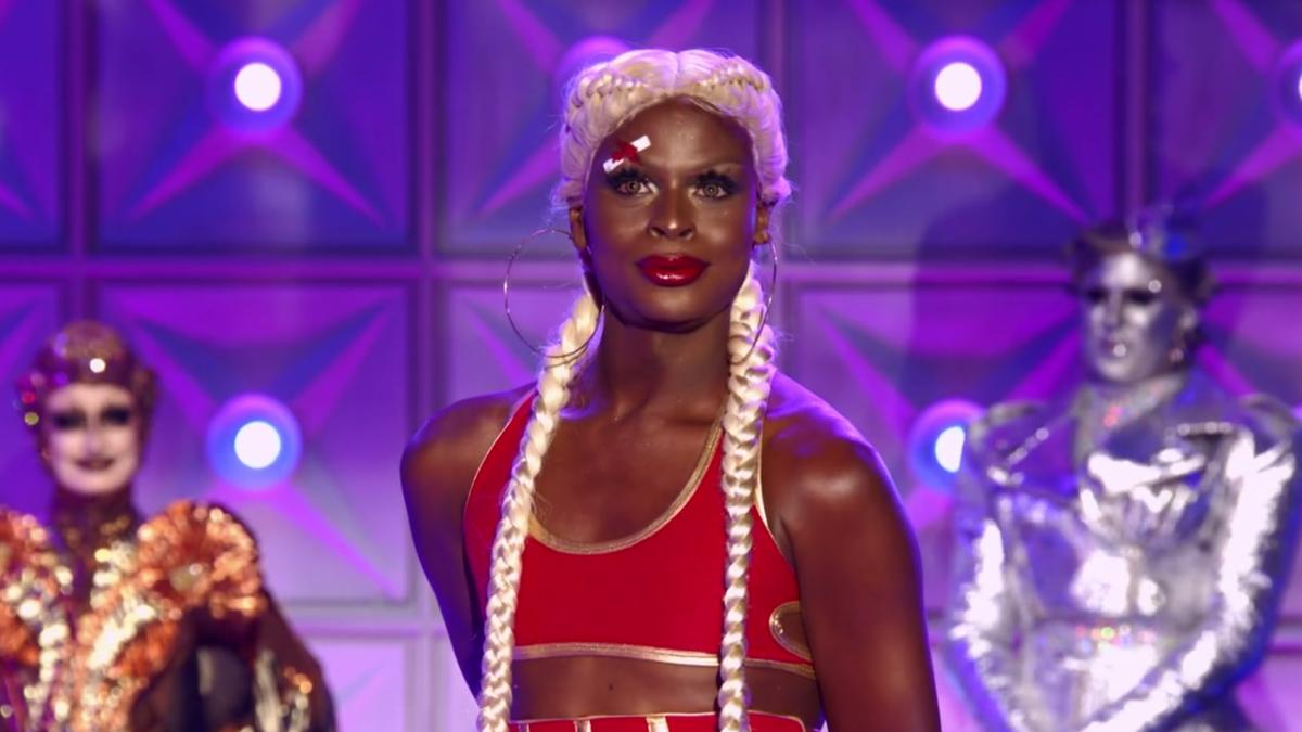 Cena da 13ª temporada do reality show RuPaul's Drag Race. Nela, vemos Symone, de roupa de boxeador, e tranças loiras, sorrindo na passarela. Ao fundo, sem foco, estão Gottmik e Tina Burner.