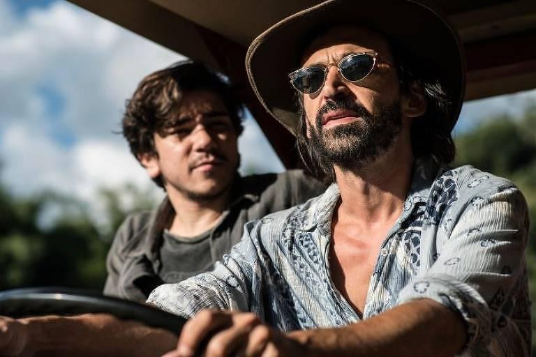 A imagem mostra Cadu e seu filho Téo dentro de um carro, no qual Cadu é o motorista. O foco da foto está em Cadu. Ele está de chapéu, óculos escuro, azul e branca. Téo é um menino branco, de cabelo castanho e bigode. Ele veste blusa e camisa cinza.