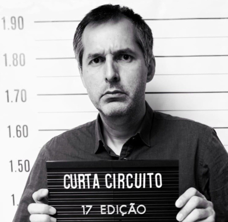 Felipe Guerra é um homem branco de 41 anos. Ele está no centro da imagem, segurando uma placa como se tivesse sendo preso, em que podemos ler CURTA CIRCUITO 17 EDIÇÃO. Ele usa uma camisa preta e a imagem é preta e branca.