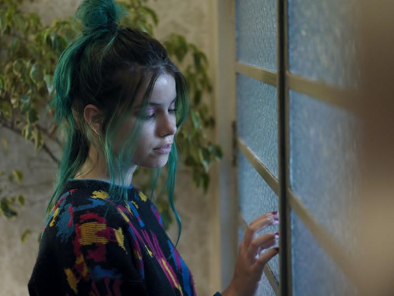 Cena do filme Me sinto bem com você. Nela, vemos Clarissa Muller com a mão em uma porta de vidro. Ela é branca, tem os cabelos verdes e veste uma roupa azul.