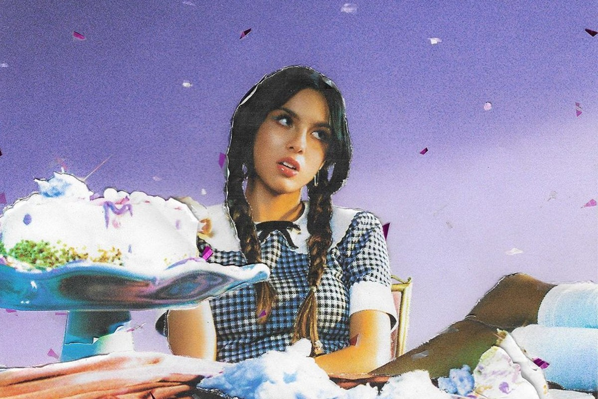 Ensaio do álbum SOUR. Num cenário roxo, Olivia Rodrigo, garota de pele clara e traços filipinos, usa tranças e tem uma expressão azeda no rosto. Ela veste um vestido azul e branco com padrão de estampa quadriculada, e está sentada à uma mesa com bolo e doces.