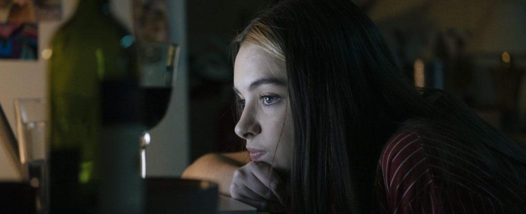 Cena do filme Me sinto bem com você. Nela, vemos Bel Moreira, branca e de cabelos castanhos, cabisbaixa na frente da tela do computador, ao lado de uma garrafa de vinho.
