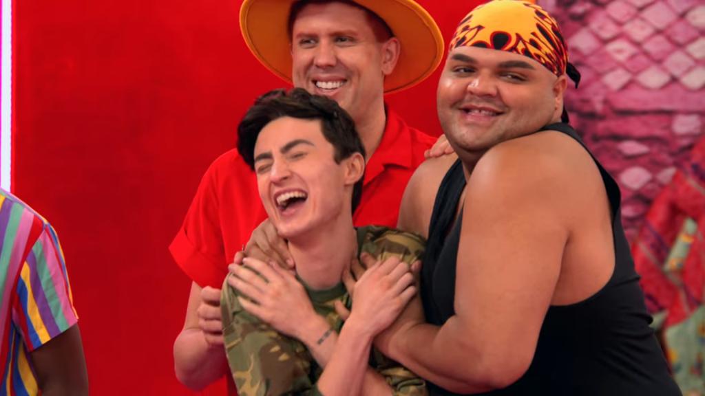 Cena da 13ª temporada do reality show RuPaul's Drag Race. Nela, vemos Gottmik, Kandy Muse e Tina Burner, no Ateliê, desmontadas. Elas sorriem e se abraçam, num gesto de carinho e amizade.