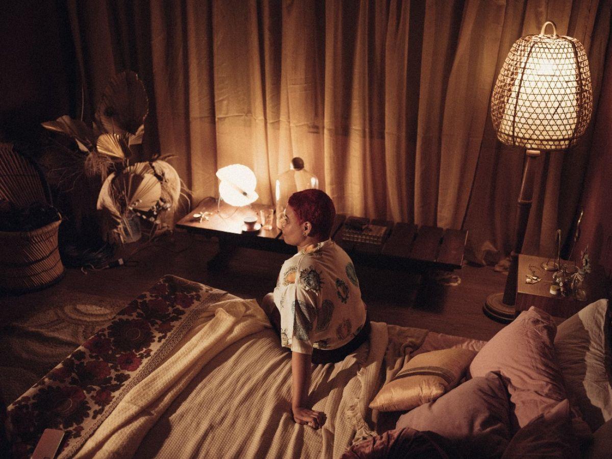 Cena do filme Me sinto bem com você. Nela, vemos Amanda Benevides sentada em sua cama. Ela é negra, gorda e tem cabelos ruivos, estilo corte joãozinho. Ela está de costas para a câmera, e o ângulo da cena é de cima.