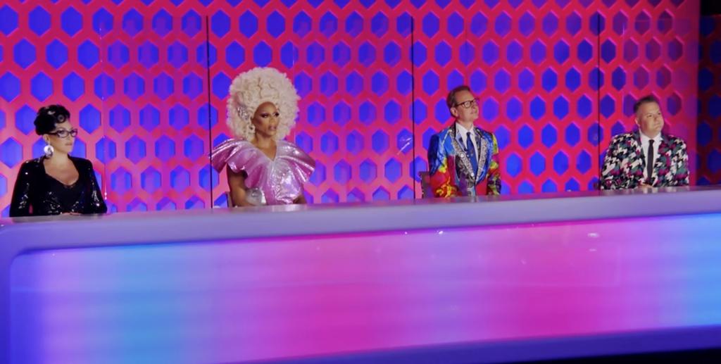 Cena da 13ª temporada do reality show RuPaul's Drag Race. Nela, vemos o painel dos jurados, socialmente distantes. Da esquerda para a direita estão Michelle Visage, RuPaul, Carson Kressley e Ross Mathews.