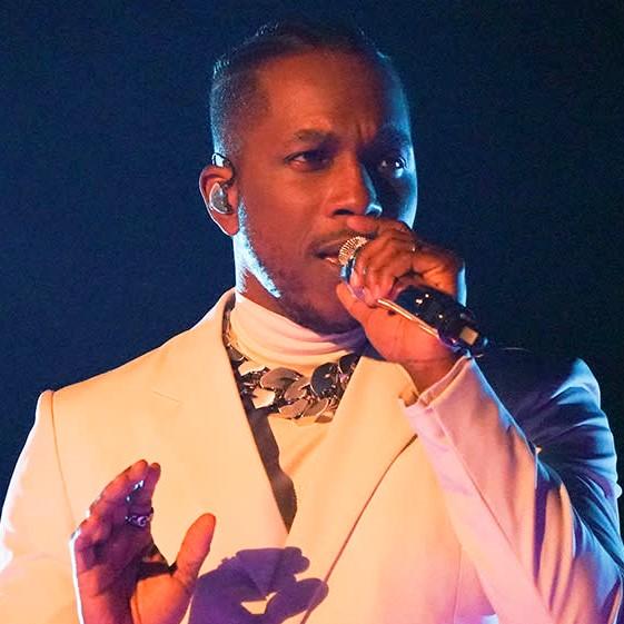 Imagem retangular da apresentação de Leslie Odom Jr. Leslie é um homem negro de 33 anos. Ele usa um terno branco com um calor prateado. Sua mão direita está levantada, e a esquerda segura um microfone.