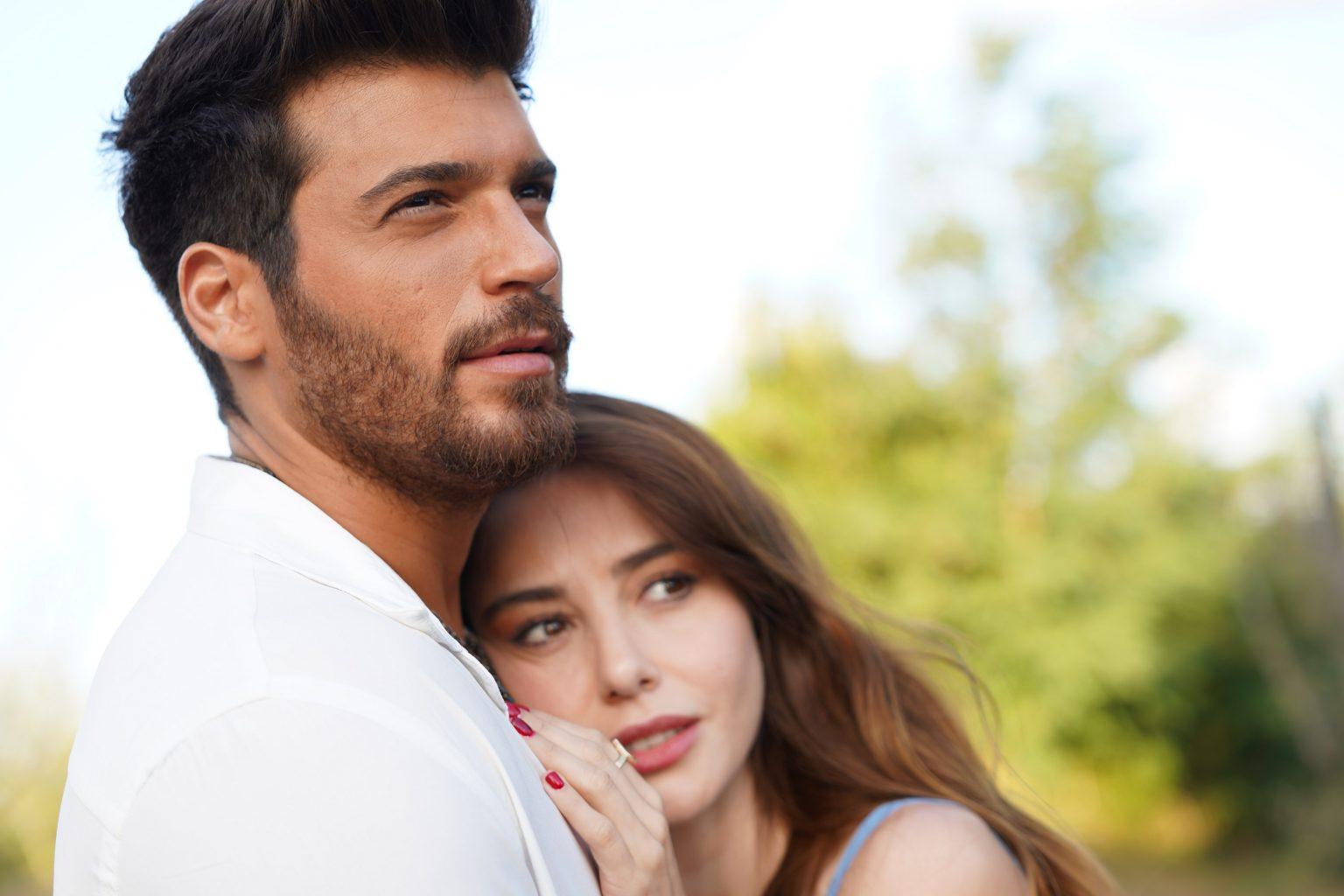 Cena da novela Bay Yanlis. Na imagem, os protagonistas estão abraçados, com Ezgi está encostada com a cabeça no peito de Özgür. Ele veste uma camisa branca e olha para a frente, enquanto a personagem feminina veste uma blusa de alças.