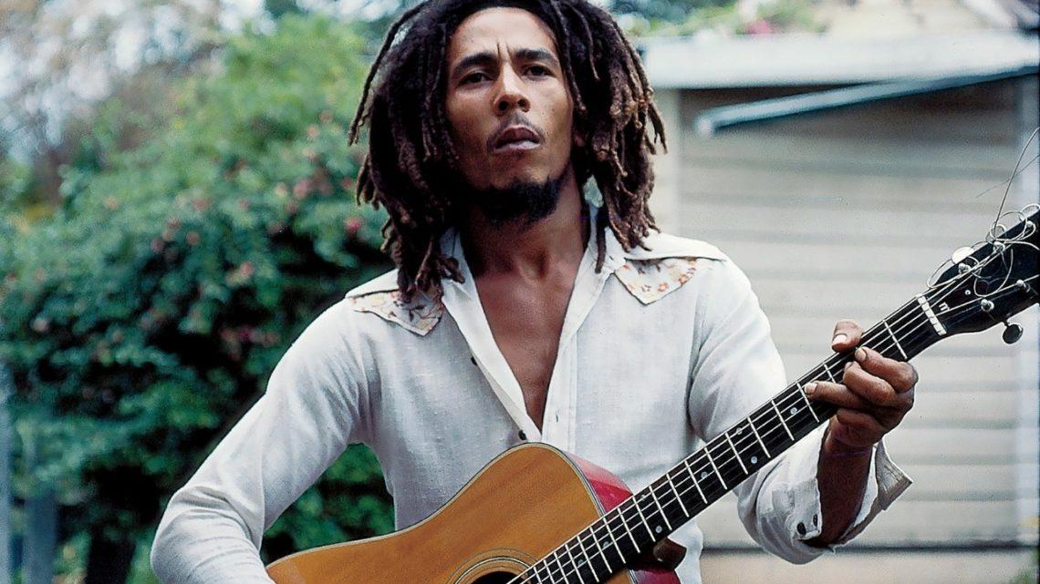 A imagem retangular mostra Bob Marley centralizado na foto. Ele é um homem negro, com dreadlocks, barba rala e cheia ao mesmo tempo, um rosto magro que olha para fora da foto. Ele usa uma camiseta de manga longa aberta no peito, similar as roupas de Elvis. A imagem o corta pelo meio enquanto ele segura e dedilha um violão de madeira clara. Ao fundo vemos uma garagem e uma mata com flores.