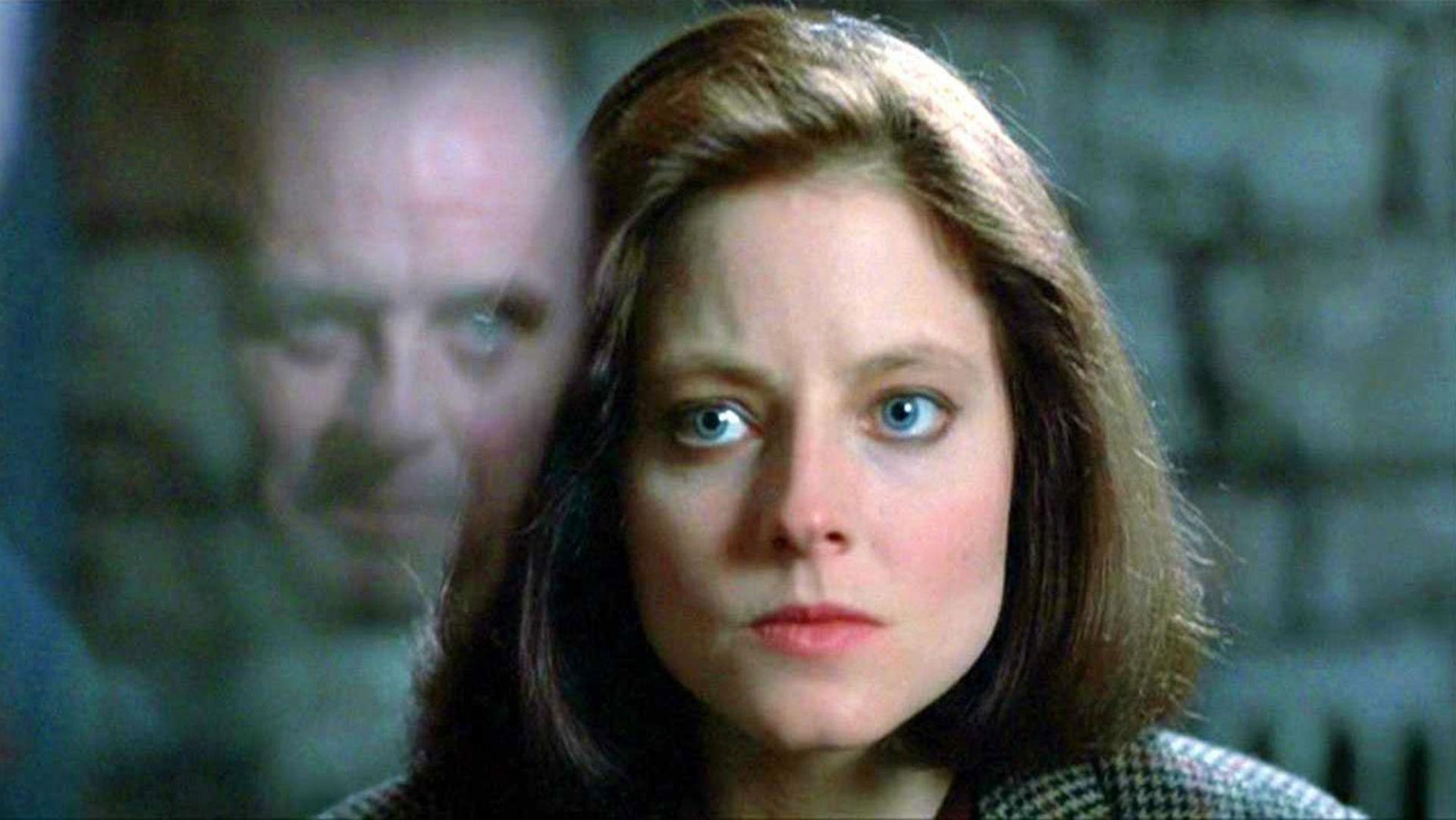 Cena do filme O Silêncio dos Inocentes. Jodie Foster está no centro da imagem. Ela é uma mulher branca de 30 anos com olhos azuis, cabelo liso e castanho até os ombros. Podemos vê-la do pescoço para cima. A sua frente, refletido no vidro, vemos o rosto de Anthony Hopkins, se sobrepondo ao de Foster. Ele a encara.