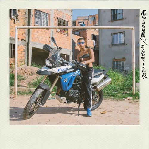 Capa do álbum JOVEM OG, do Febem, fotografia quadrada com casas de palafita ao fundo e uma trave de futebol, no centro da imagem um homem negro com o rosto embaçado, ele usa um óculos azul e está em cima de uma moto em um campo de futebol na terra.