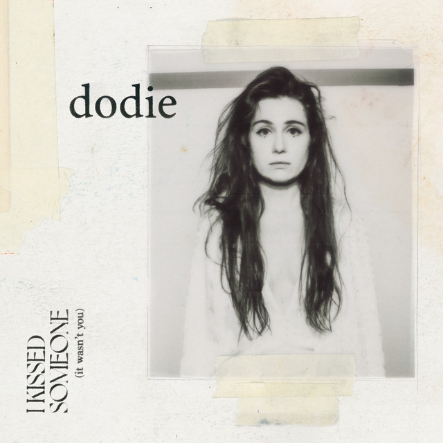 Foto de capa do EP I Kissed Someone (It Wasn't You), de Dodie. A imagem é quadrada, possui um fundo branco, com textura de papel. No canto superior esquerdo, há uma fita crepe que parece estar remendando o papel; ao lado vemos o nome da cantora, Dodie, que sobrepõe uma foto em preto e branco colada no papel com fita crepe. Na foto, está Dodie em preto e branco; ela é uma mulher branca, de 26 anos, que possui longos cabelos castanhos e usa um vestido branco. No canto inferior esquerdo está escrito o nome do EP.