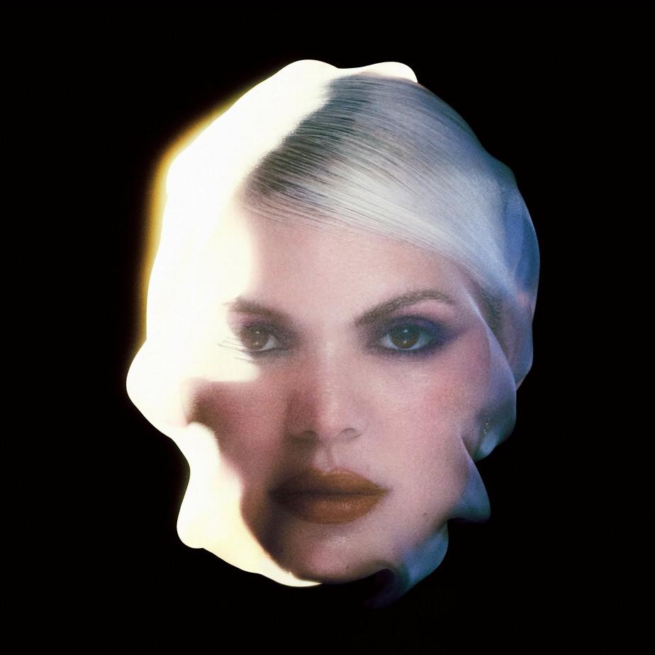 Capa do álbum Te Amo Lá Fora de Duda Beat. Na imagem, o rosto de Duda Beat aparece sobre um fundo preto. Ele está coberto de chamas do lado esquerdo. Duda é uma mulher branca, seu cabelo é loiro e ela está maquiada com um delineador azul. Sua expressão é séria.