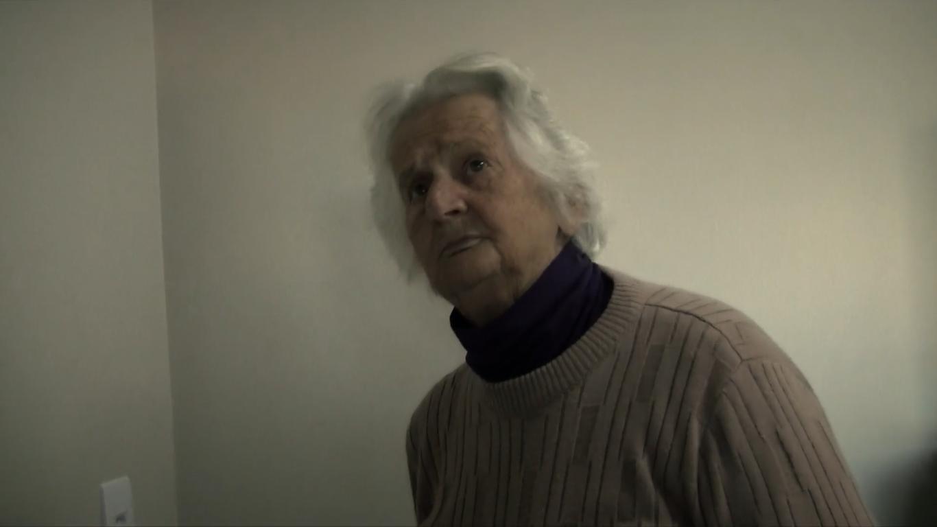 Cena do curta Dona Oldina Vai Às Compras. Dona Oldina está no centro da imagem, da região do peito para cima. Ela é uma senhora branca de 90 anos com cabelos na região do ombro, tam´bem brancos. Ela usa um suéter bege e uma blusa gola alta roxa. Ela olha para cima.