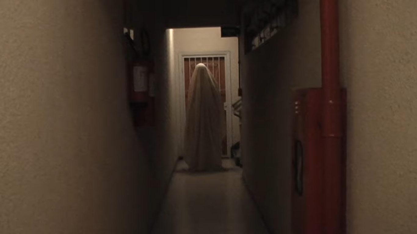 Cena do curta Blanket. No fim de um corredor de paredes brancas, vemos uma figura em pé com um lençol branco cobrindo o corpo todo, parado de frente ao corredor. Nas paredes, vemos extintores de incêndio e kits de segurança.