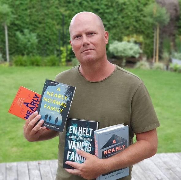 Fotografia de M.T. Edvardsson. M.T. está no centro da imagem e segura quatro livros em suas mãos - diversas versões de sua obra Uma família quase perfeita. Ele é um homem branco, de meia idade e careca e usa uma camiseta simples verde. Ao fundo, vemos um grande jardim.