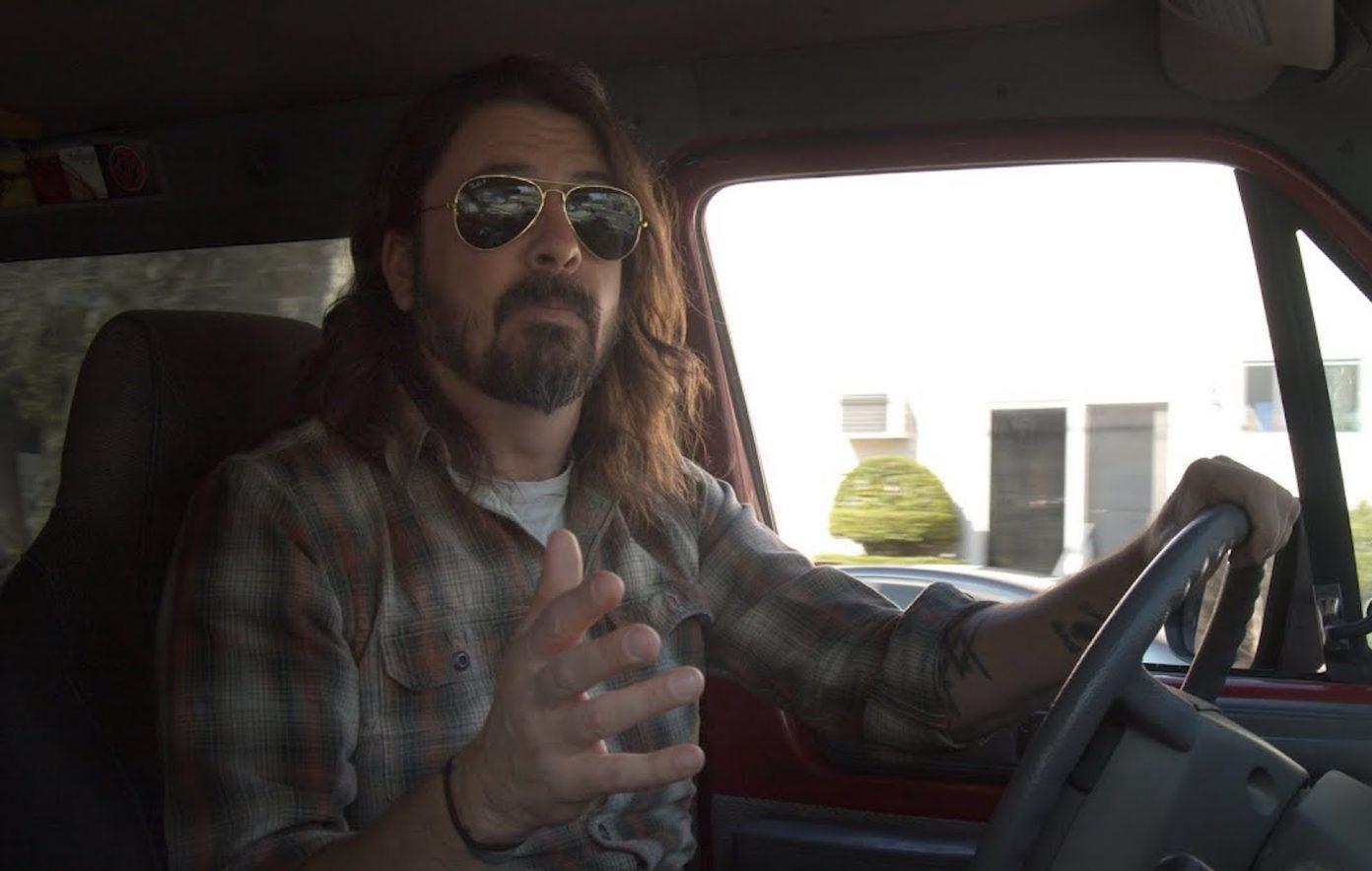 Cena de What Drives Us. Dave Grohl, um homem branco de 52 anos, está sentado no banco de motorista dentro de um carro. Ele possui cabelos comrpidos e castanhos, barba e bigode castanhos e usa óculos escuros. Dave usa camisa listrada e está com a mão esquerda no volante, olhando para a câmera.