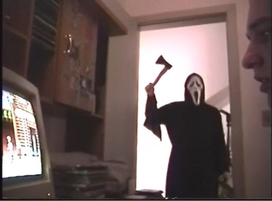 Cena do filme Entrei em Pânico ao Saber o que Vocês Fizeram na Sexta-Feira 13 do Verão Passado. Um assassino segurando um machado olha por dentro de uma porta, na ddireção de um jovem que está mexendo no computador.